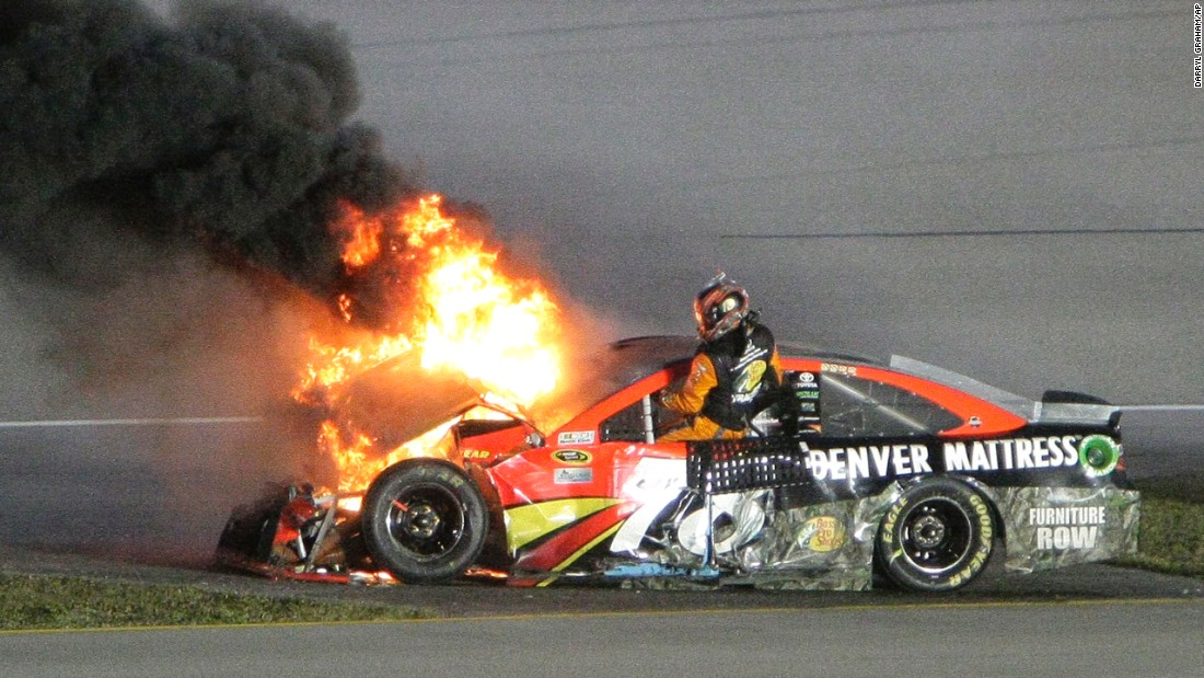 Martin Truex Jr. gets out of his flaming car after crashing in the NASCAR season's final Sprint Cup race on Sunday, November 20.