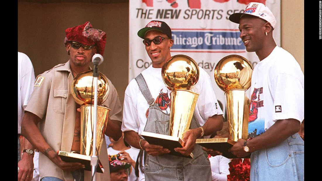 Rodman, left, holds one of the three championship trophies he won with the Bulls.