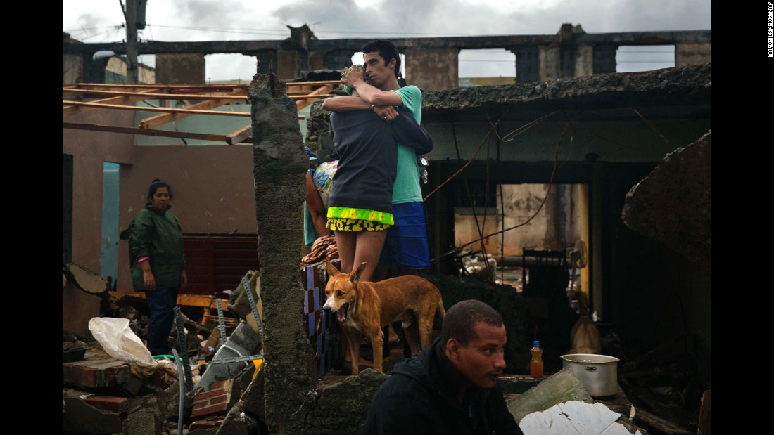 People embrace at their damaged home in Baracoa, Cuba, on Wednesday, October 5. Hurricane Matthew rolled across the sparsely populated tip of Cuba, destroying dozens of homes in the country's easternmost city and leaving hundreds of others damaged.