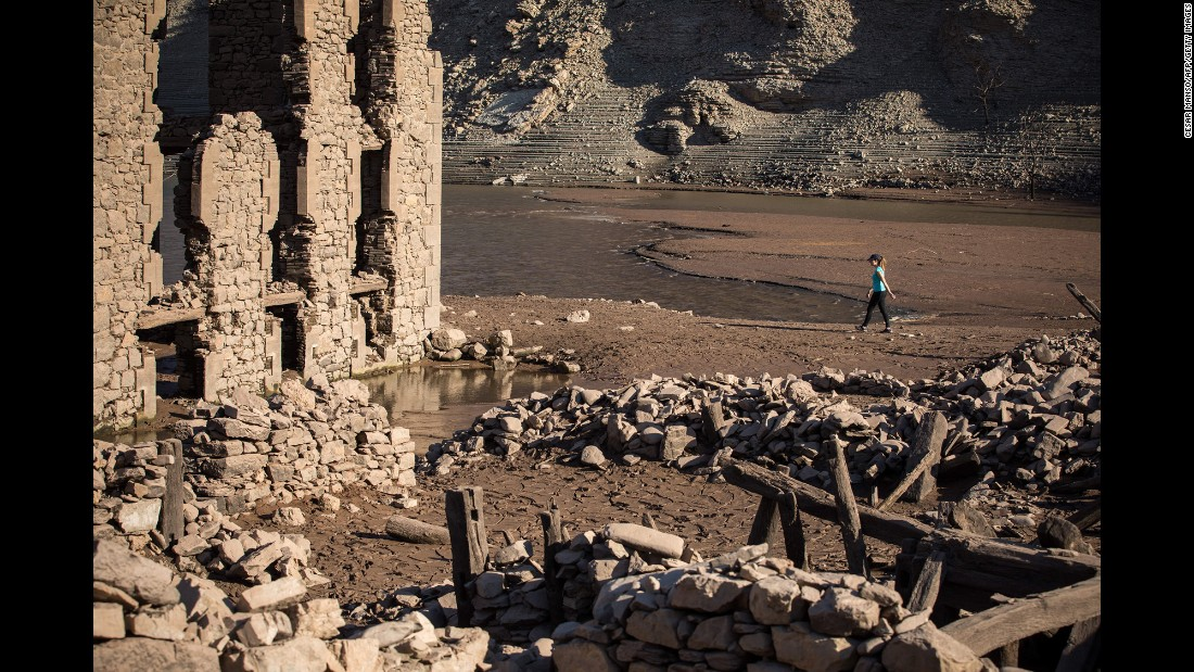A woman walks through the remains of the former Spanish town of Mansilla on Saturday, October 8, after a lack of rain dropped the water level in the Mansilla Reservoir.