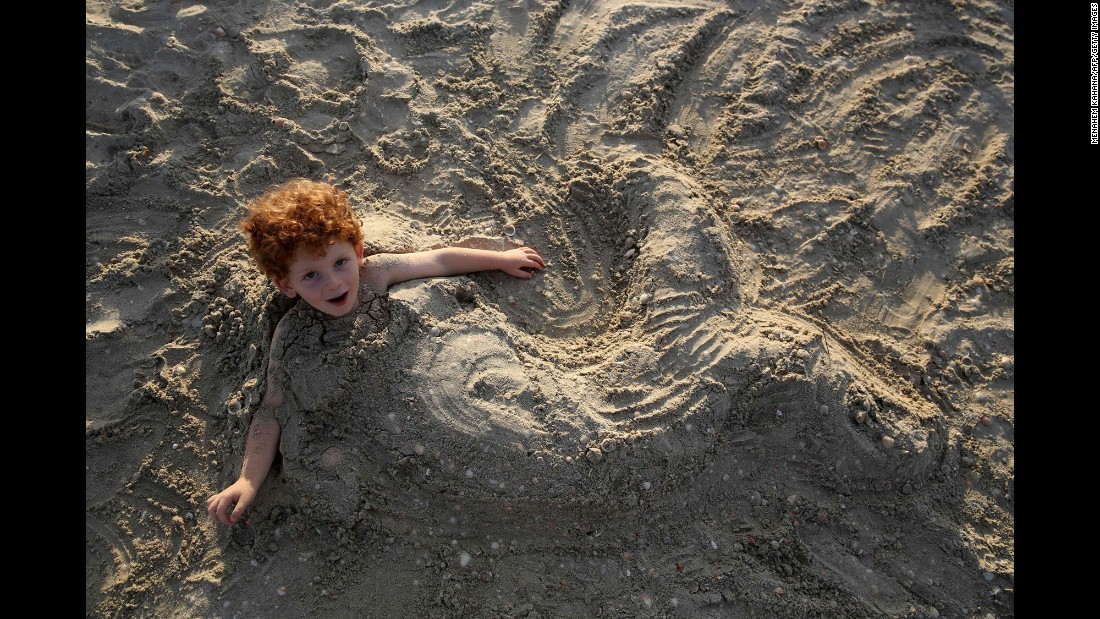 A boy is buried under the sand as he spends time at the beach near the Israeli village of Habonim on Monday, October 10.