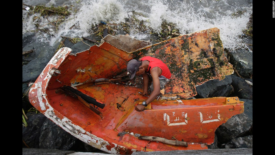 "Joybin Marayo salvages metal from a damaged boat that was washed ashore by <a href=""http://www.cnn.com/2016/10/18/asia/typhoons-haima-philippines/"" target=""_blank"">Typhoon Haima</a> in Manila, Philippines. Haima, the second typhoon to hit the Philippines in less than a week, made landfall on Wednesday, October 19."