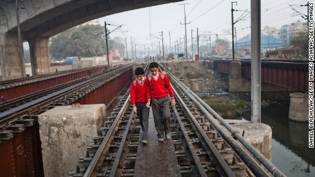Boys walk to school over railway tracks close to the Nizamuddin Railway Station in New Delhi, India.