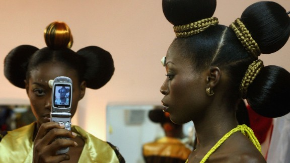 At a time when Africa is hosting the COP22, the mobile phone sector has had a catastrophic environmental impact in the region.  Pictured: Nigerian fashion models Mary Jane Unueroh and Fome Emede (L) take a photo of themselves with a cell phone behind the curtain during their fashion show  to promote ethnic fashion in Tel Aviv, Israel.