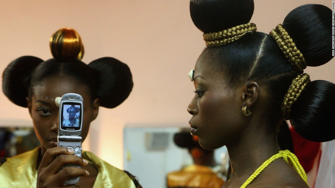 At a time when Africa is hosting the COP22, the mobile phone sector has had a catastrophic environmental impact in the region.<br /><br />Pictured: Nigerian fashion models Mary Jane Unueroh and Fome Emede (L) take a photo of themselves with a cell phone behind the curtain during their fashion show  to promote ethnic fashion in Tel Aviv, Israel.
