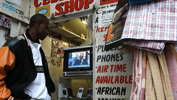"""""""The digital recycling sector, relating to the life-cycle of all high-tech products, must be completely re-examined, cleaned up, made viable and profitable in the long run throughout the continent,"""" say academics.   Pictured: A mobile phone shop worker watches a televised broadcast of the Nelson Mandela memorial service on December 10, 2013 in Johannesburg, South Africa."""
