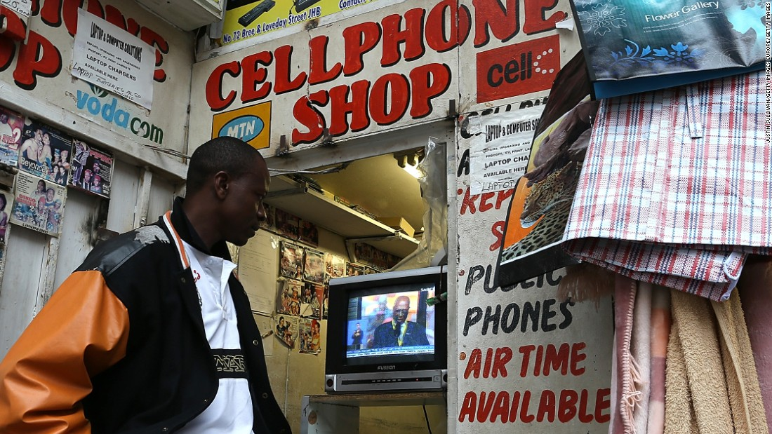 """The digital recycling sector, relating to the life-cycle of all high-tech products, must be completely re-examined, cleaned up, made viable and profitable in the long run throughout the continent,"" say academics. <br /><br />Pictured: A mobile phone shop worker watches a televised broadcast of the Nelson Mandela memorial service on December 10, 2013 in Johannesburg, South Africa."