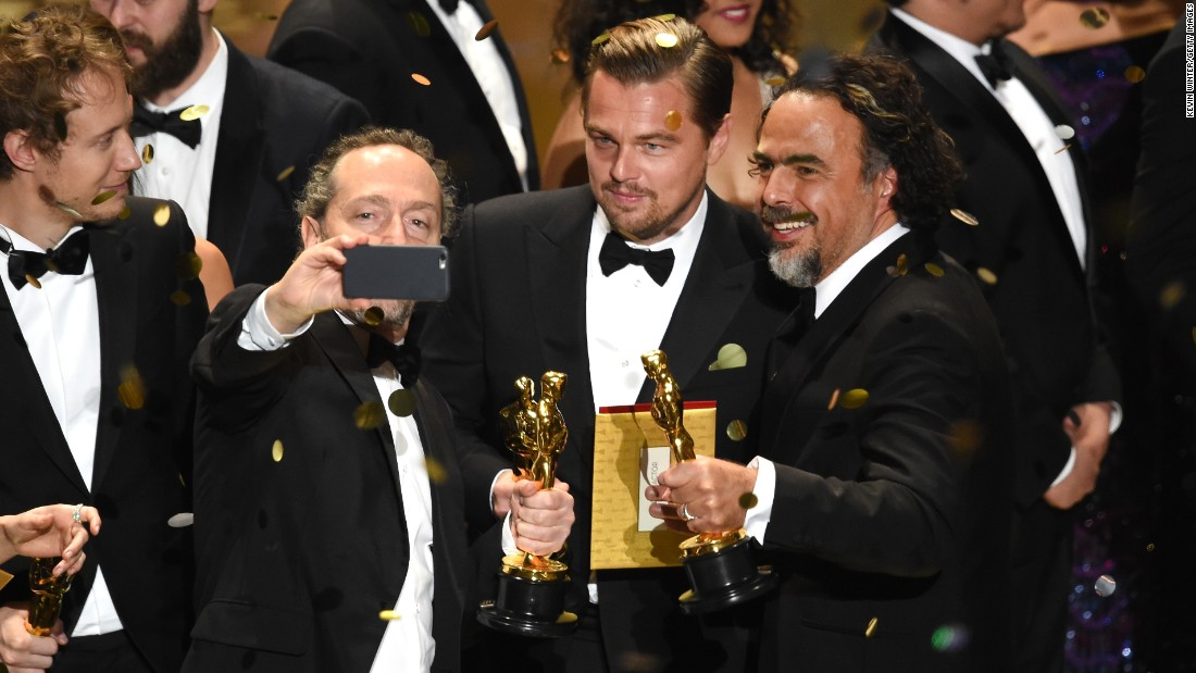"Cinematographer Emmanuel Lubezki takes an on-stage selfie with actor Leonardo DiCaprio and director Alejandro Gonzalez Inarritu during the Academy Awards on Sunday, February 28. All three won Oscars for ""The Revenant."""