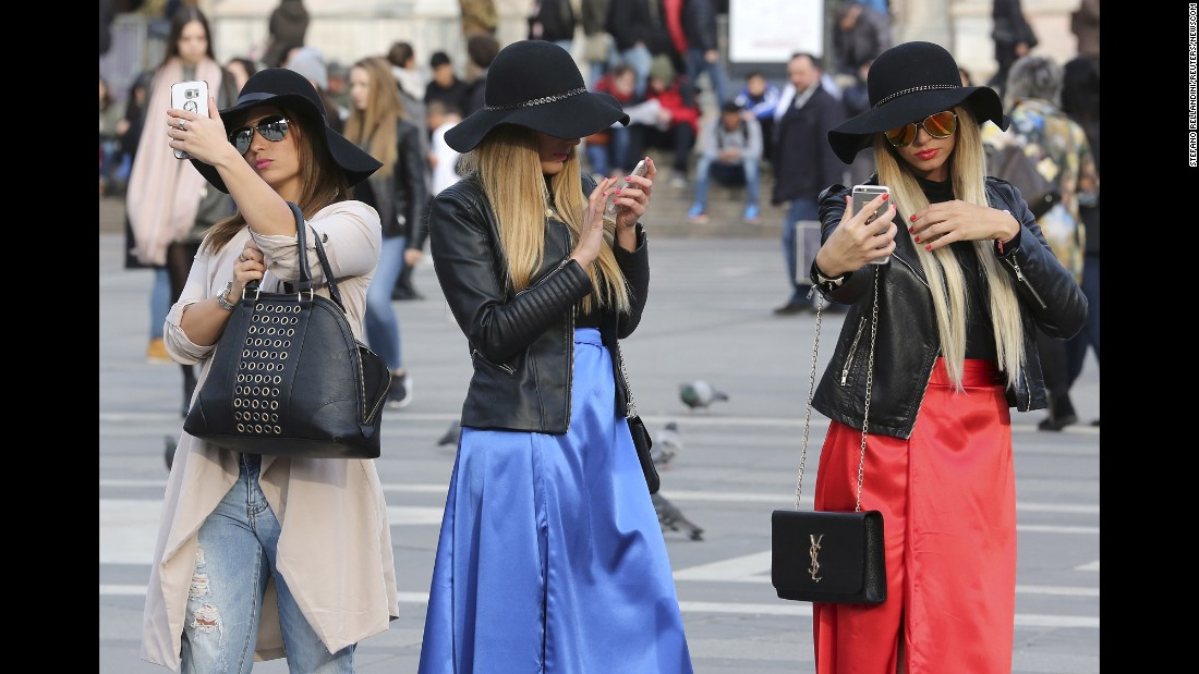 Women use their cell phones in Milan, Italy, on Thursday, February 25.