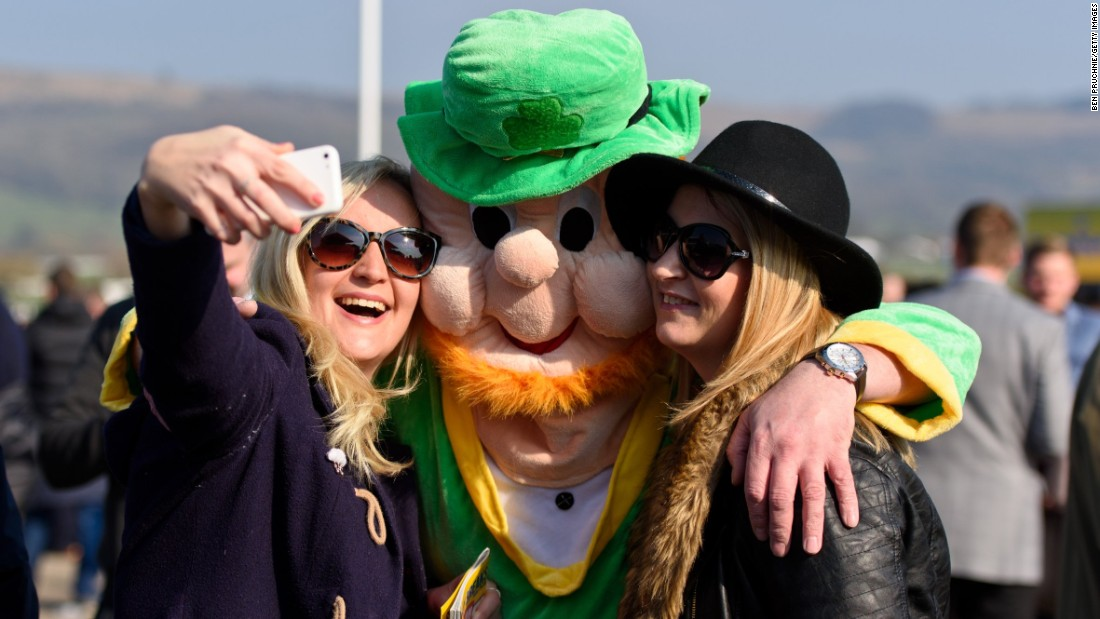Women in Cheltenham, England, pose with a person in a leprechaun suit on St. Patrick's Day.
