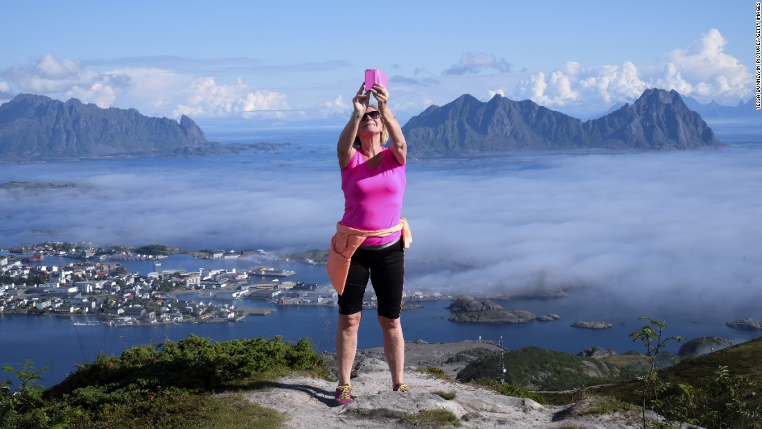 A woman takes a selfie atop a mountain in Norway's Lofoten islands on Sunday, August 21.