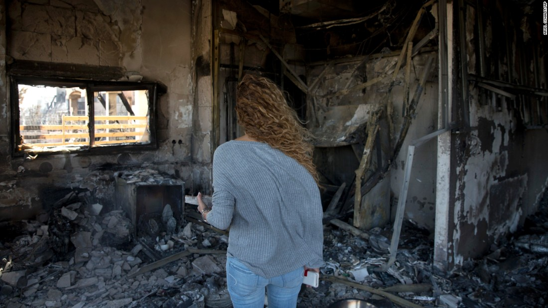 Relly Golan surveys the ruins of her burned home in Zikhron Ya'akov on November 23.