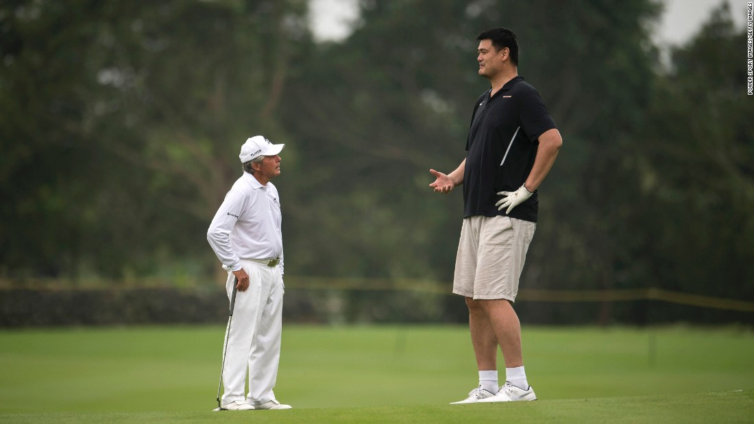 Golf legend Gary Player, left, and basketball Hall of Famer Yao Ming talk during a celebrity pro-am in Haikou, China, on Sunday, October 23. Yao is 7 feet, 6 inches -- a full 2 feet taller than Player.