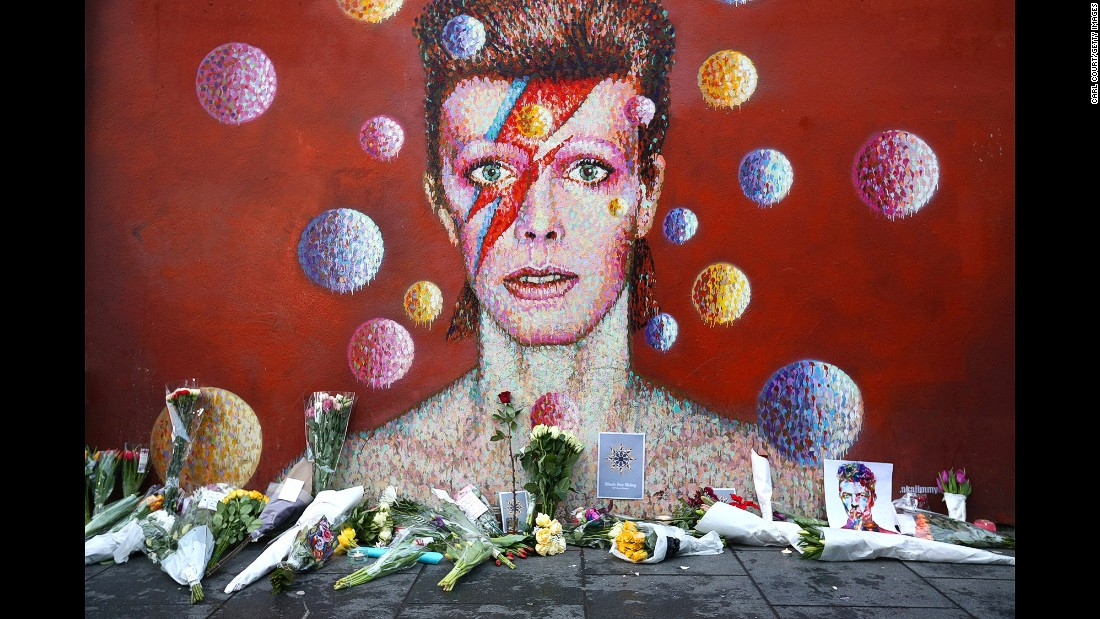 "Flowers are laid beneath a mural of David Bowie in London on Monday, January 11. <a href=""http://www.cnn.com/2016/01/11/entertainment/david-bowie-thr-obit/index.html"" target=""_blank"">The rock legend died</a> a day earlier at the age of 69."