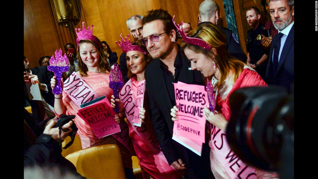 U2 lead singer Bono poses with protesters at a Senate subcommittee in Washington on Tuesday, April 12. The singer urged officials to provide more aid to refugees, saying it would help in the fight against violent extremism.