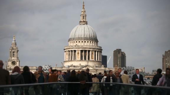 Pedestrians walk along the Millennium Bridge with St Paul