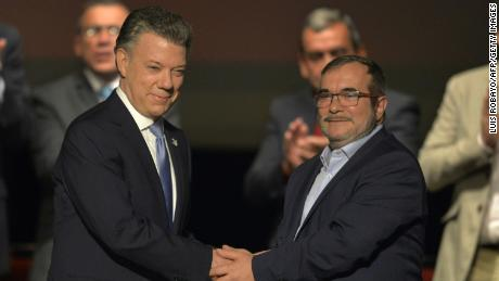 Colombian President Juan Manuel Santos and the head of the FARC guerrilla Timoleon Jimenez, aka Timochenko, shake hands during the second signing of the historic peace agreement between the Colombian government and the Revolutionary Armed Forces of Colombia at the Colon Theater in Bogota, Colombia, on November 24.
