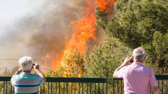 Two people document a Haifa fire on their cell phones on November 24.
