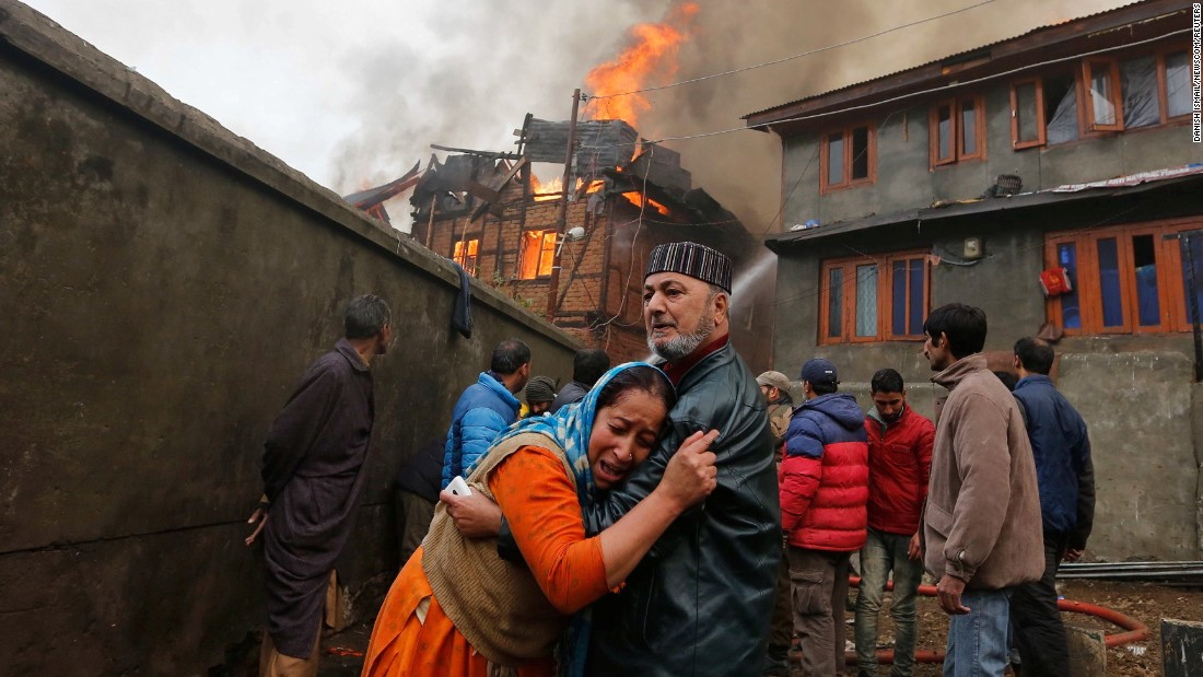 A woman is consoled by a relative after her house in Srinagar, India, was damaged by a fire on Monday, November 21