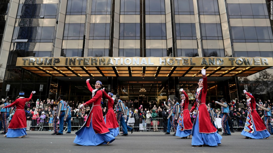 Dancers wave to spectators as they walk past the Trump International Hotel and Tower.