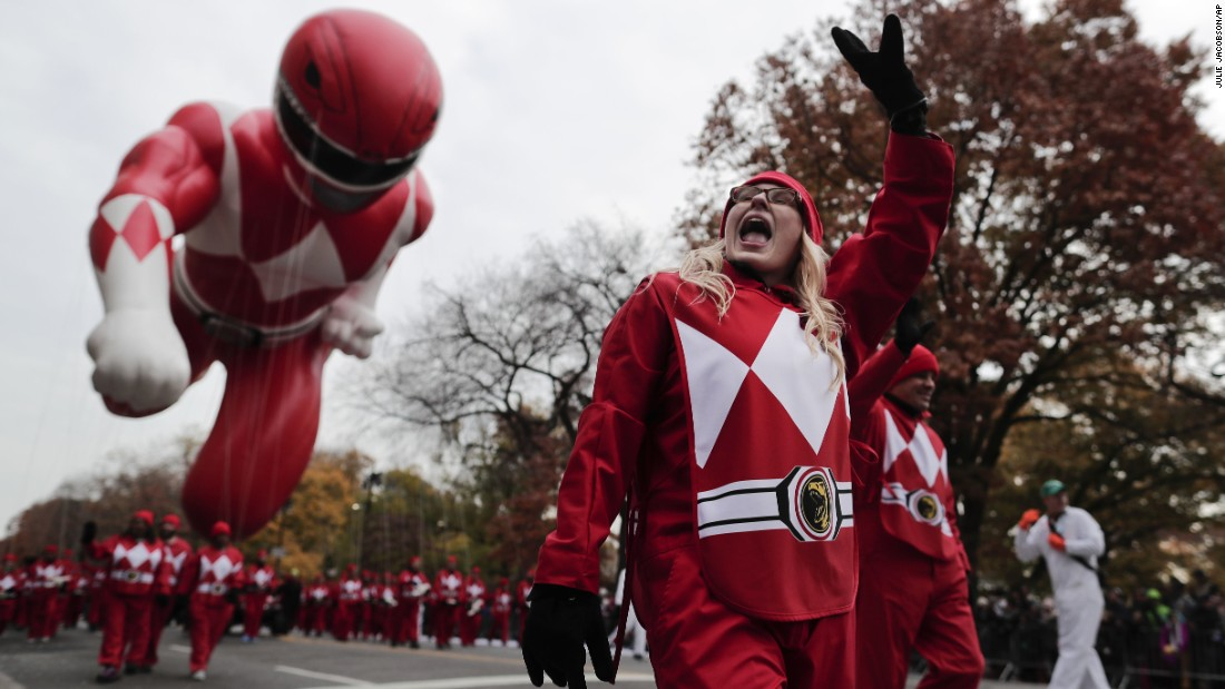 A balloon operator waves to spectators while guiding the Red Power Ranger.
