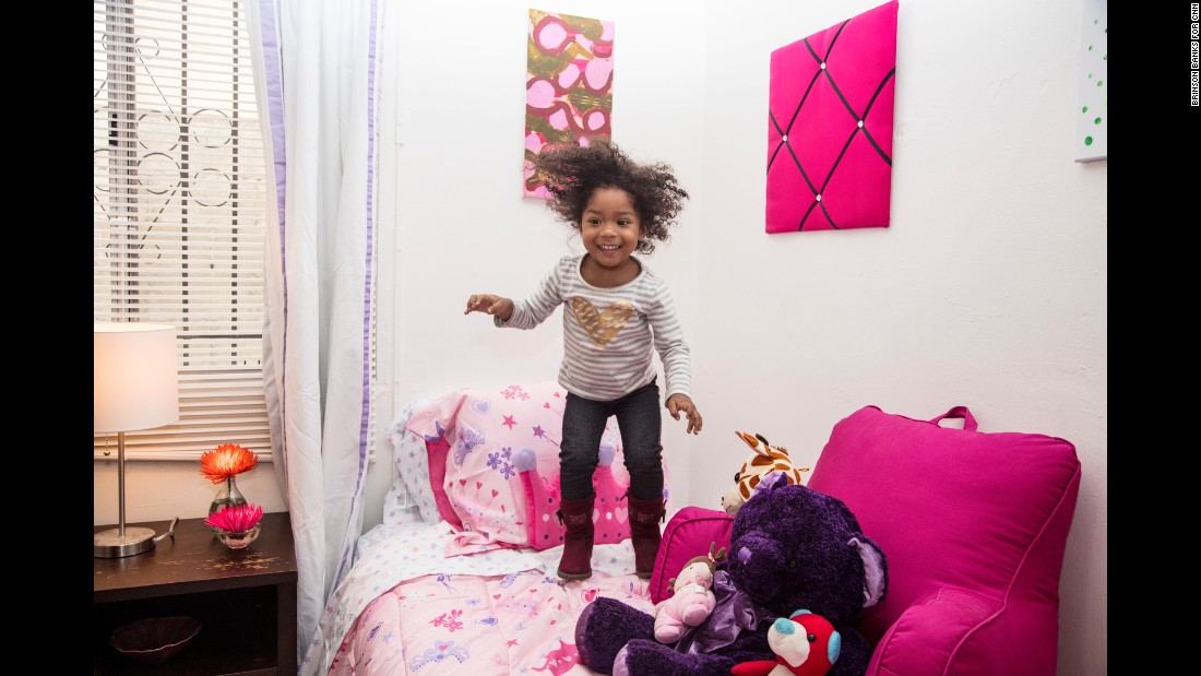 Ja'el jumps on a pink bed in her new apartment in Los Angeles. Art is an important component to making a house a home, Smith said.