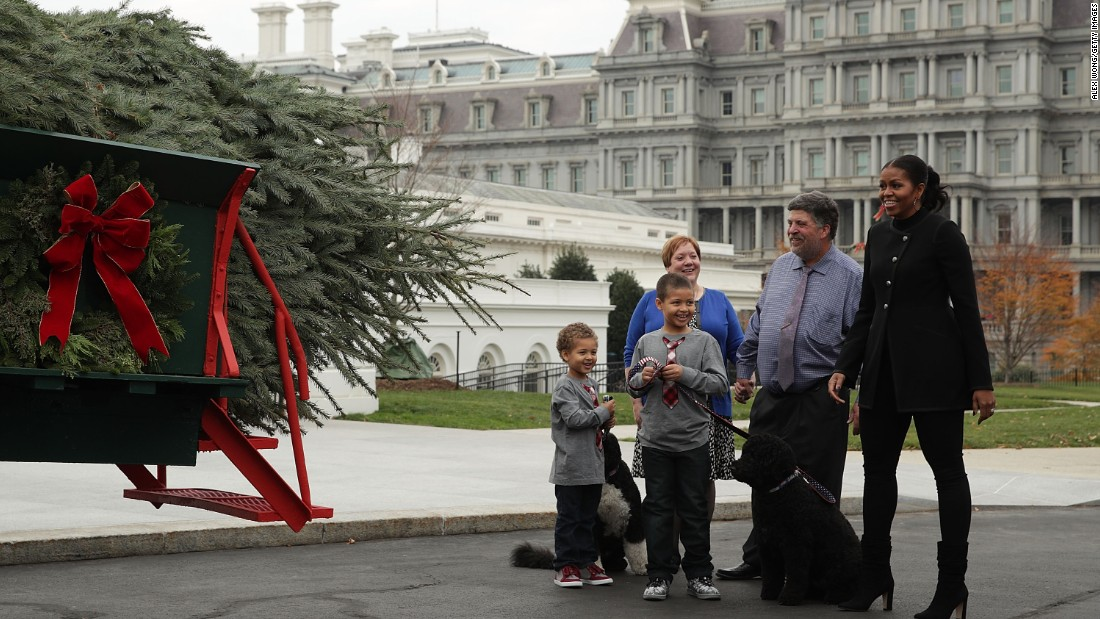First lady Michelle Obama, accompanied by her nephews Austin and Aaron Robinson and her dogs, Bo and Sunny, is presented with the official White House Christmas tree by Dave and Mary Vander Velden of Oconto, Wisconsin, at the North Portico of the White House on November 25, 2016.