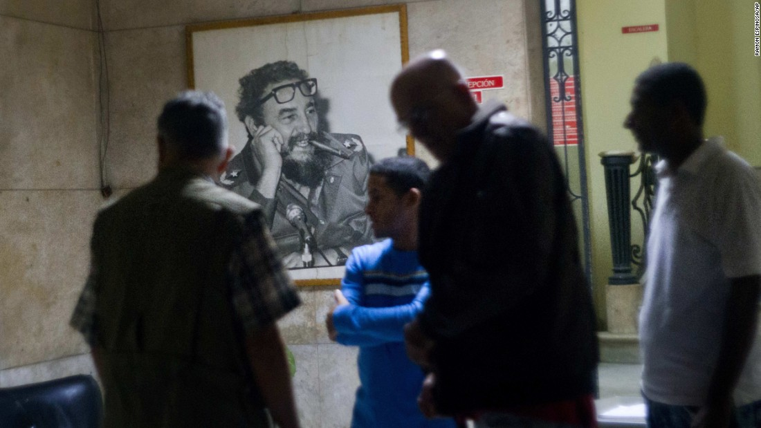 People gather at an office of the Popular Assembly in Havana in front of a picture of the iconic leader on November 26 after President Raul Castro announced his brother's death on television.