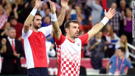 Croatia's tennis players Ivan Dodig (center) and Marin Cilic celebrate their doubles victory in the Davis Cup final.