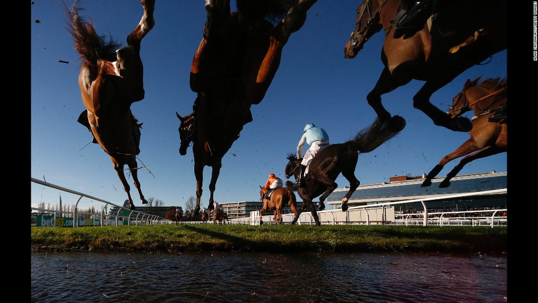Horses clear a water jump during a steeplechase race in Newbury, England, on Friday, November 25.