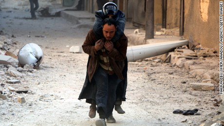 A man helps evacuate a wounded victim after airstrikes in al-Shear, Aleppo, on Monday.