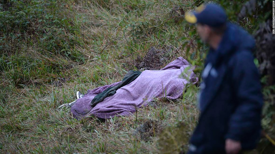 A rescuer walks past a victim's body on Tuesday, November 29.