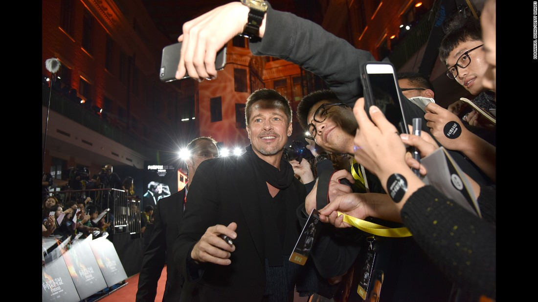 "Actor Brad Pitt poses for a fan's red-carpet selfie at the ""Allied"" premiere in Shanghai, China, on Monday, November 14."
