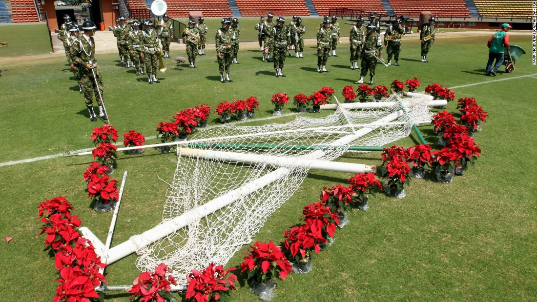 The posts of a soccer goal are decorated with flowers while members of a Colombian army band rehearse for the tribute in Medellin on November 30.