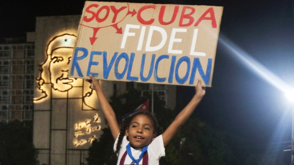 """A girl in Havana holds a sign that reads """"I am Cuba. I am Fidel. I am revolution"""" on Tuesday, November 29."""