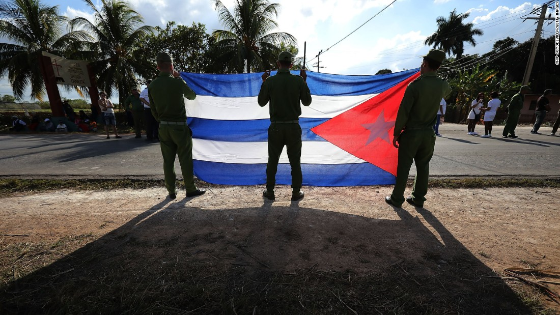 Ministry of Interior troops hold a Cuban flag as they wait for the military caravan transporting Castro's remains on November 30.