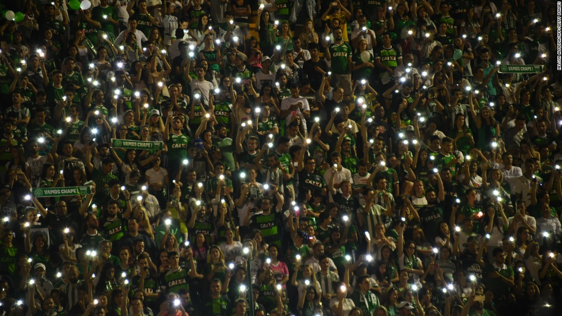 Fans of the team hold their cell phones in the air during the tribute.