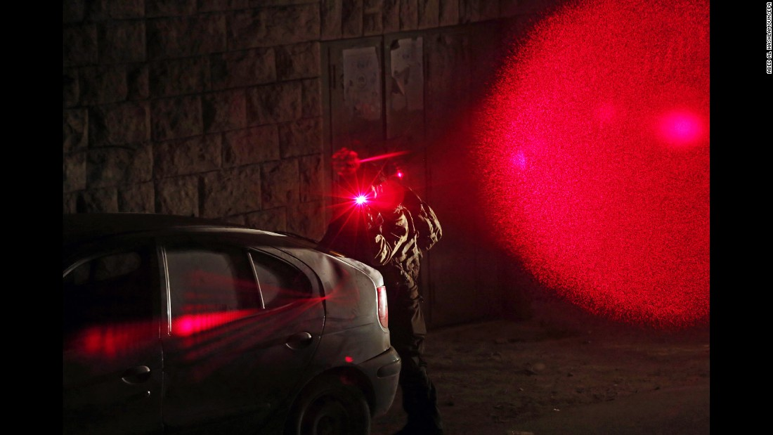 "<strong>June 15:</strong> An Israeli army soldier aims his laser sight at a camera during a night raid in Hebron, West Bank. The army was carrying out raids in the West Bank, searching houses and making arrests a week after <a href=""http://www.cnn.com/2016/06/08/middleeast/israel-tel-aviv-shooting/"" target=""_blank"">terrorists killed four Israelis</a> at a popular food and shopping complex in Tel Aviv, Israel."