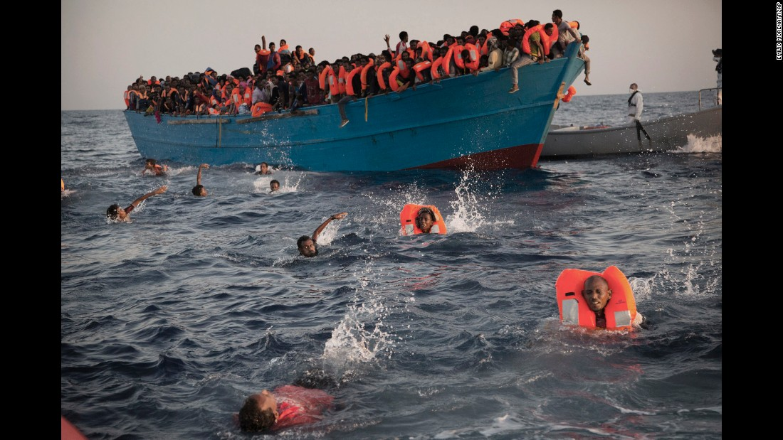 <strong>August 29:</strong> Migrants swim away from a crowded wooden boat as they are rescued in the Mediterranean Sea north of Sabratha, Libya. Thousands were rescued from more than 20 boats.