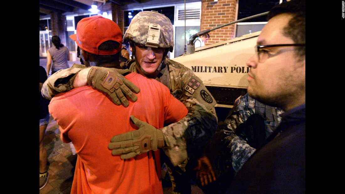"<strong>September 22:</strong> A protester embraces a member of the National Guard in Charlotte, North Carolina. Violent protests <a href=""http://www.cnn.com/2016/09/21/us/gallery/charlotte-protest/index.html"" target=""_blank"">erupted in Charlotte</a> following the death of Keith Lamont Scott, who was shot by police in an apartment complex parking lot. Charlotte-Mecklenburg Police Chief Kerr Putney said Scott exited his car with a gun and that he was shot after he wouldn't drop it. Scott's family said he was unarmed and sitting in his car reading a book. A two-month investigation <a href=""http://www.cnn.com/2016/11/30/us/keith-lamont-scott-case-brentley-vinson/"" target=""_blank"">later determined that the police officer was justified</a> in shooting Scott and that ""all the credible evidence"" led to the conclusion that Scott was armed. Mecklenburg County District Attorney Andrew Murray said he didn't reach the conclusions alone; a total of 15 prosecutors unanimously agreed with the decision."