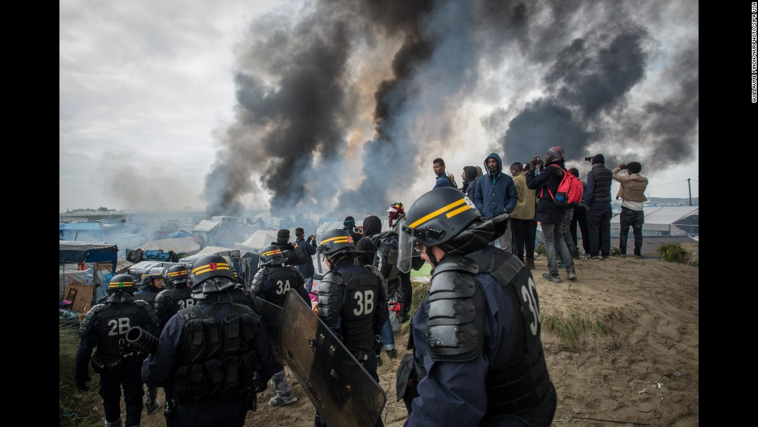 "<strong>October 26:</strong> Smoke rises from <a href=""http://www.cnn.com/2016/09/26/europe/gallery/the-saga-of-the-calais-jungle/index.html"" target=""_blank"">""The Jungle,""</a> a makeshift migrant camp in Calais, France, that authorities <a href=""http://www.cnn.com/2016/10/26/europe/calais-jungle-france-close/"" target=""_blank"">began dismantling</a> on October 24. During evacuations, some of the migrants set shelters on fire. By the middle of the week, more than 4,400 people had been bused out of Calais to other regions of the country. The town is known for being a major transit point for migrants trying to reach Great Britain."
