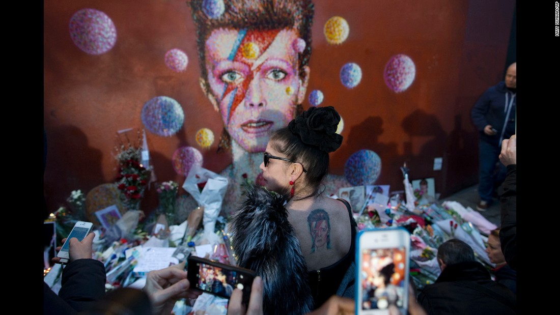 "<strong>January 11:</strong> A woman with a David Bowie tattoo poses in front of a Bowie mural in London. The rock legend <a href=""http://www.cnn.com/2016/01/11/entertainment/david-bowie-death/"" target=""_blank"">died a day earlier</a> after an 18-month battle with cancer. He was 69."