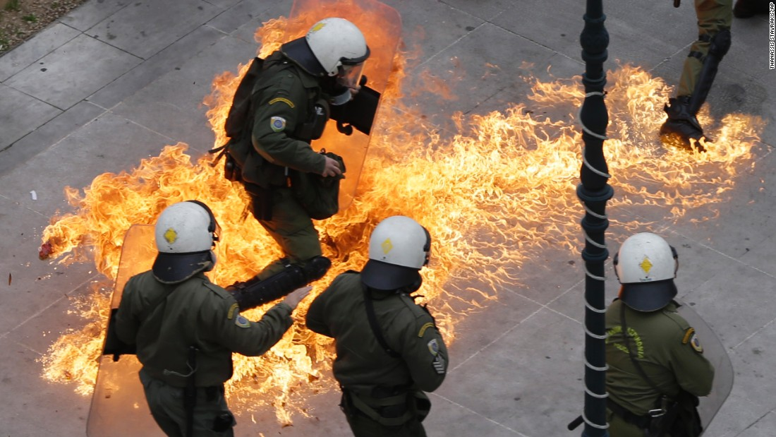 <strong>February 4:</strong> Riot police in Athens, Greece, try to avoid a Molotov cocktail thrown by protesters during a nationwide strike. Clashes broke out as tens of thousands of people protested pension reforms that were part of the country's latest economic bailout.