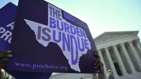 An abortion rights activist holds placards outside of the US Supreme Court before the Court struck down a Texas law placing restrictions on abortion clinics on June 27, 2016 in Washington, DC.