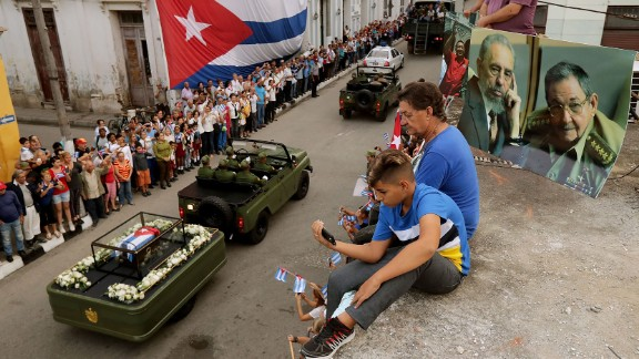 People watch from a rooftop as Castro's remains pass by in Santa Clara on December 1. Castro's ashes are on a four-day journey from Havana to Santiago de Cuba.