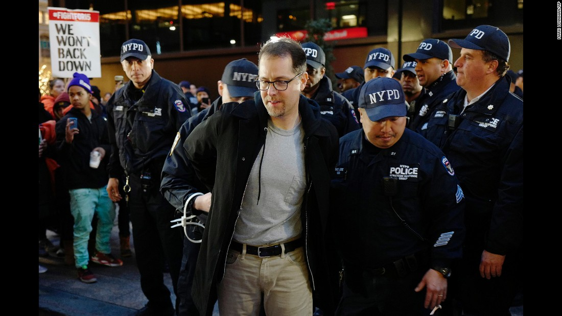 "A man is detained by police in New York after he and other protesters blocked Broadway on Tuesday, November 29. Dozens of people were arrested during <a href=""http://money.cnn.com/2016/11/29/news/minimum-wage-protest-arrests/"" target=""_blank"">nationwide demonstrations</a> for a $15 minimum wage."