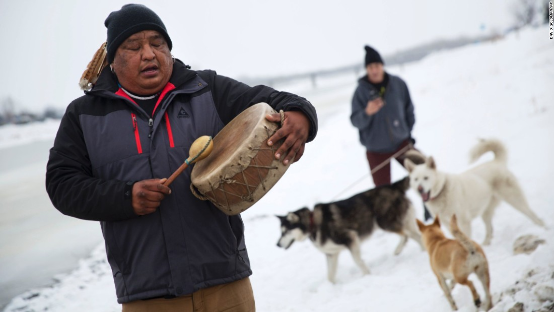 Dan Nanamkin of the Colville Nez Perce tribe drums a traditional song by the Cannonball River in Cannon Ball, North Dakota, on Thursday, December 1.