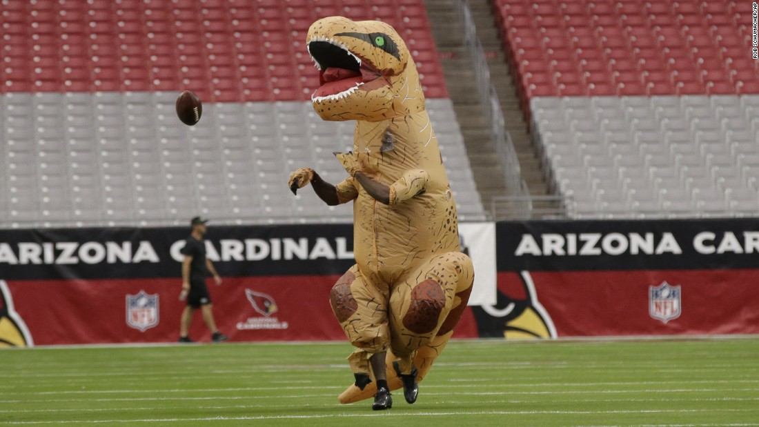 "Arizona cornerback Patrick Peterson, dressed up as a dinosaur, warms up before an NFL game against the New York Jets on Monday, October 17. It was <a href=""http://www.nfl.com/news/story/0ap3000000723066/article/patrick-peterson-preps-for-game-in-dinosaur-costume"" target=""_blank"">his punishment</a> for losing a friendly throwing competition."