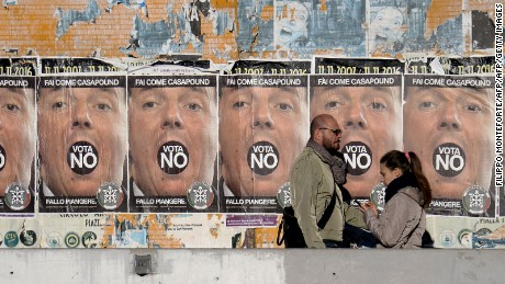"People walk past posters for far-right political movement CasaPound, which is calling for a ""No"" vote."