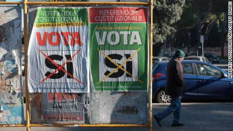 "A man walks past posters calling for a ""Yes"" vote in Italy's constitutional referendum."